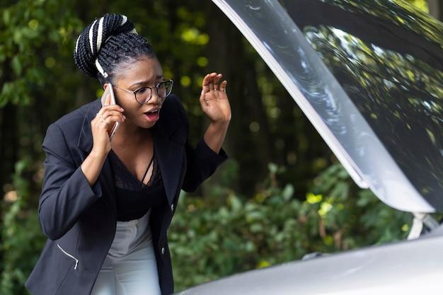 車のエンジンが機能していないことについて電話で話している動揺した女性 無料写真