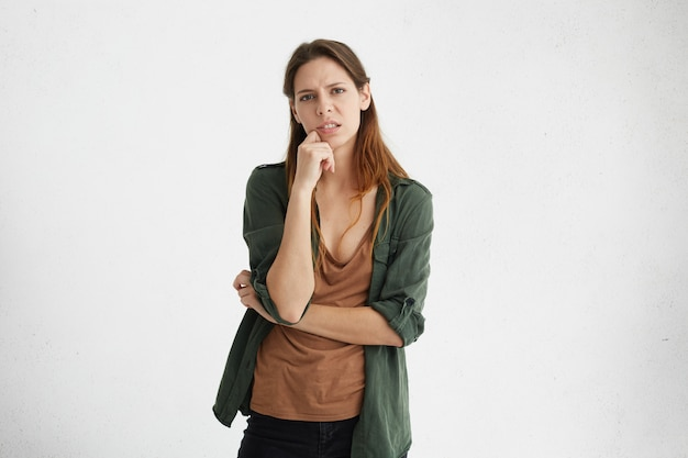 カジュアルな茶色のtシャツと緑のジャケットを着て疲れた不幸な顔をしたあごに手を握って美しい外観を持つ動揺の女性。 無料写真