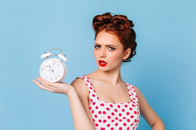 Upset woman with bright makeup showing time. studio shot of beautiful pinup girl with clock. Free Photo