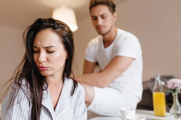 Donna sconvolta con capelli lisci castani in posa a casa con uomo triste sullo sfondo Foto Gratuite