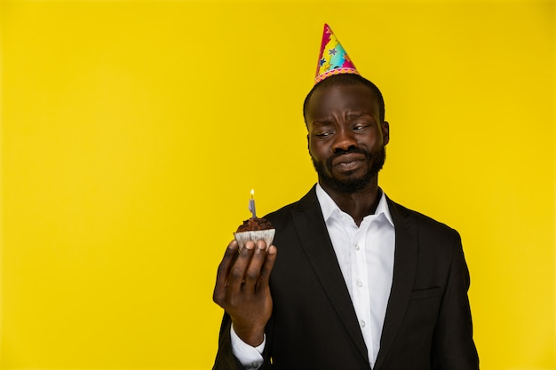 Upset young afroamerican guy in black suit and birthday hat with burning candle Free Photo