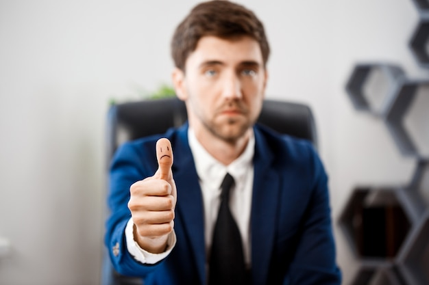 Upset young businessman showing okay at workplace. Free Photo