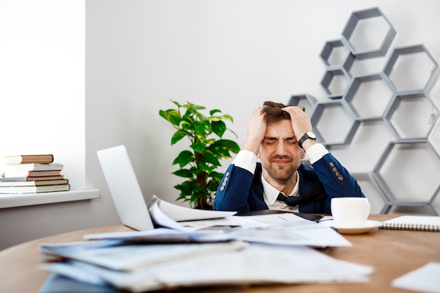 Upset young businessman sitting at workplace, office background. Free Photo