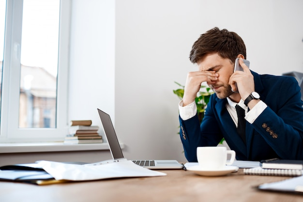 Upset young businessman speaking on phone, office background. Free Photo