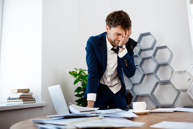 Upset young businessman standing at workplace, office background. Free Photo