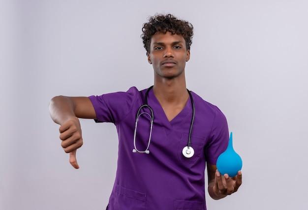 Un giovane medico dalla carnagione scura bello sconvolto con capelli ricci che indossa l'uniforme viola con lo stetoscopio che mostra i pollici giù mentre tiene un clistere Foto Gratuite