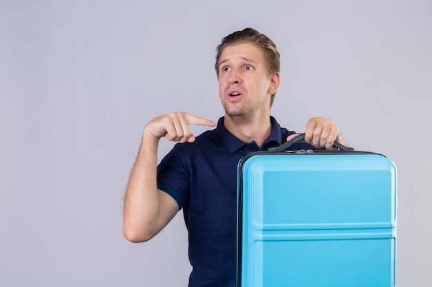 Upset young handsome traveler man holding suitcase looking away pointing finger to his suitcase standing over white background Free Photo