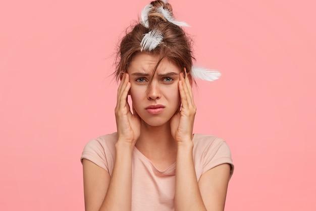 Расстроенная молодая женщина держит руки на висках, страдает головной болью, недовольно хмурится, плохо спит ночью, одетая в повседневную футболку Бесплатные Фотографии