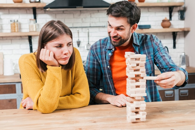 Upset young woman looking at happy man playing the wooden stack on the desk Free Photo