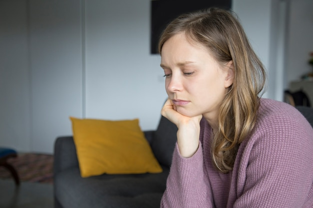 Upset young woman sitting on sofa at home, looking down Free Photo