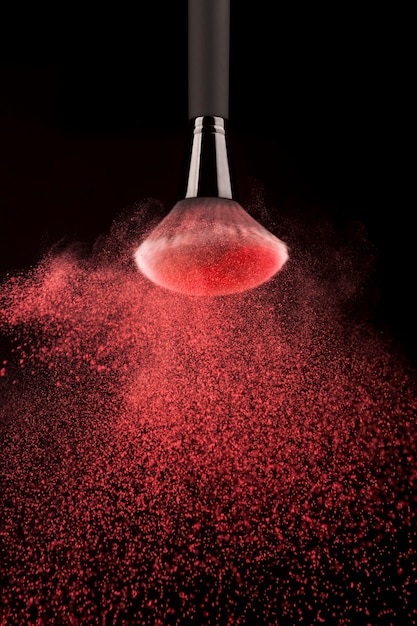Upside down makeup brush with red powder splash Free Photo
