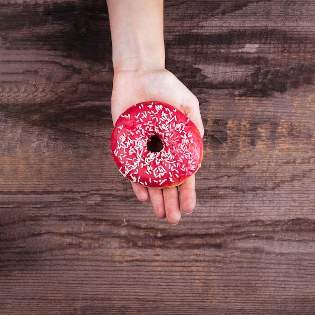 Upside down palm holding a doughnut Free Photo