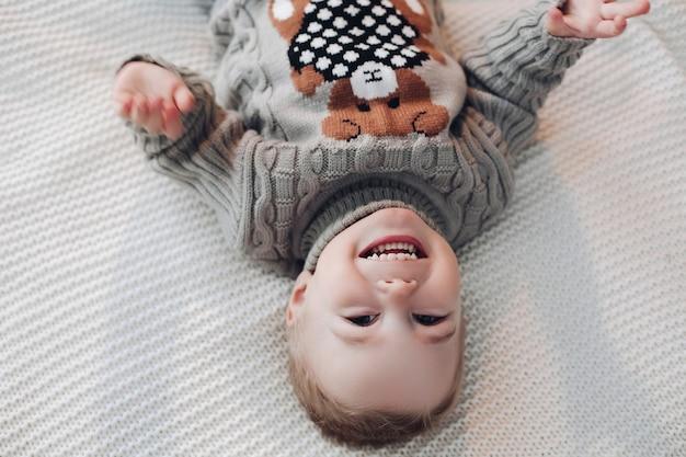 Перевернутое фото очаровательного малыша в теплом свитере, лежащего на кровати и смеющегося Бесплатные Фотографии