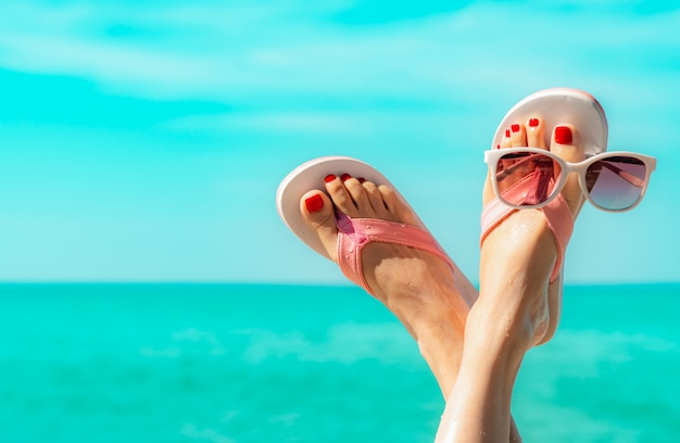 Upside woman feet and red pedicure wearing pink sandals, sunglasses at seaside. funny and happy fashion young woman relax on vacation. Premium Photo