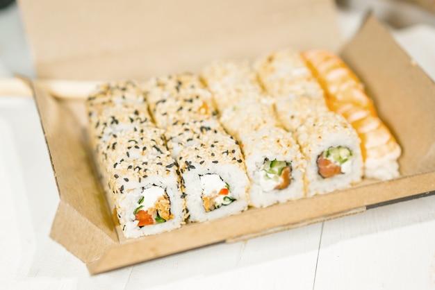 Урамаки суши роллы с кунжутом в коричневой бумажной упаковке. Premium Фотографии