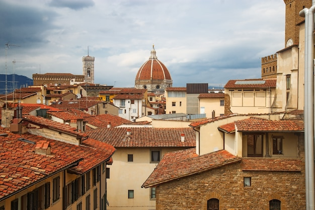 The urban landscape of florence. top view of the cathedral of saint mary of the flower and the tiled roofs of houses. Premium Photo