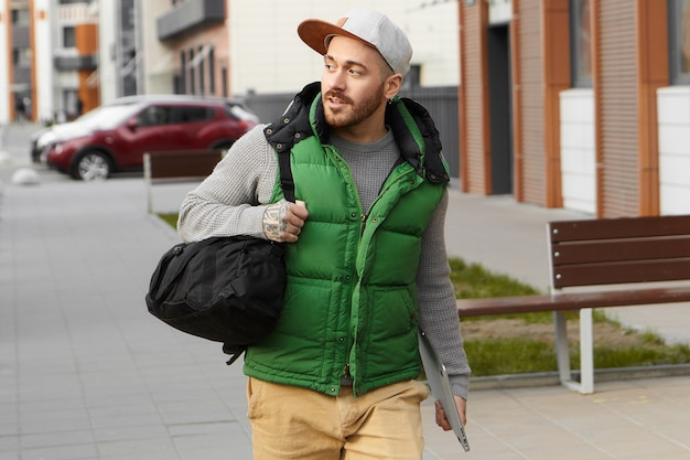 Urban lifestyle, technology and travel concept. attractive fashionable young european man with stubble wearing stylish clothes, carrying black shoulder bag and digital tablet, going on business trip Free Photo