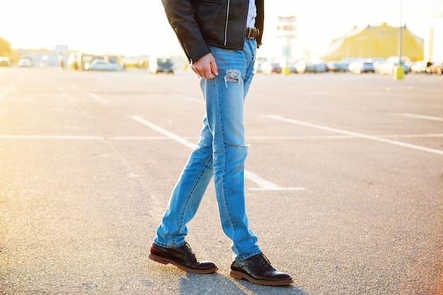 Ritratto urbano di moda all'aperto di giovane uomo alla moda hipster che indossa pantaloni in denim giacca da motociclista in pelle e scarpe vintage in posa alla luce del sole serale parcheggio campagna. Foto Gratuite