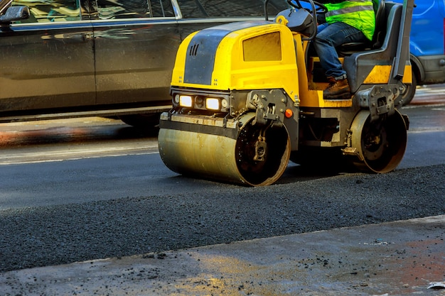 Urban road is under construction, asphalting of yellow roller Premium Photo