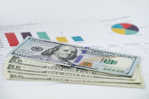 チャートグラフスプレッドシート紙の上の米ドル紙幣お金。 Premium写真