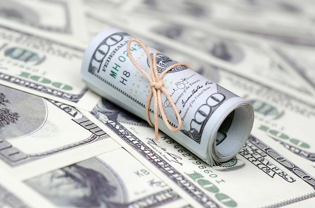 Us dollars rolled up and tightened with band lies on a lot of american banknotes with blurred background Premium Photo