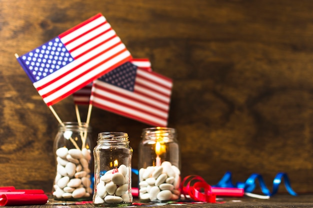 Usa american flag and lighted candles in the white candies jar on wooden desk Free Photo