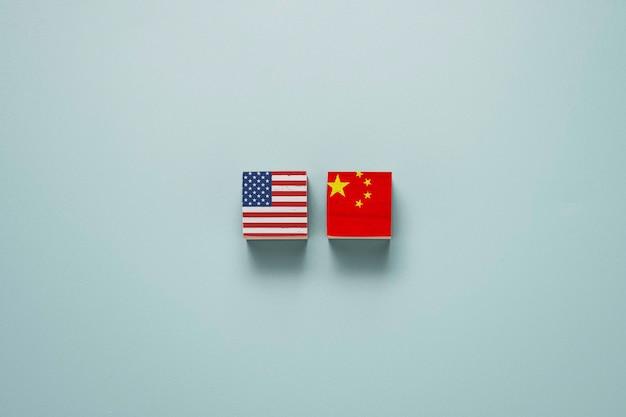 米国と中国は、青い背景の木製ブロックキューブに印刷画面を表示します。 Premium写真