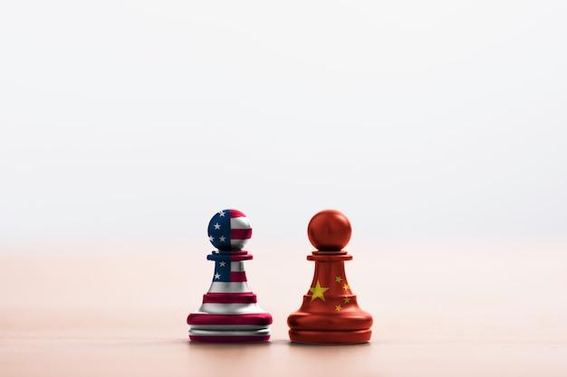 Флаг сша и флаг китая печатают экран на шахматах пешки с светлой мягкой предпосылкой. это символ тарифного барьера войны войны тарифа между соединенными штатами америки и китаем. - изображение. Premium Фотографии