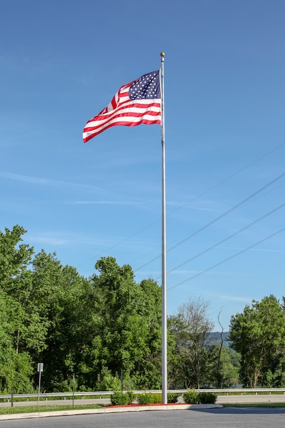 Usa flag on pole in blue sky at usa Premium Photo
