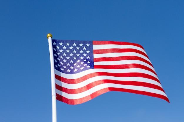 Флаг сша развевается в голубом небе. американский флаг. празднование дня независимости америки. Premium Фотографии