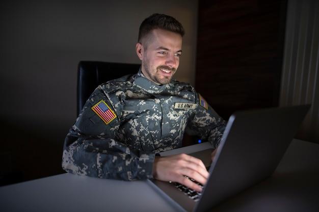 Soldato usa in uniforme che lavora fino a tardi al computer che invia posta alla sua famiglia Foto Gratuite