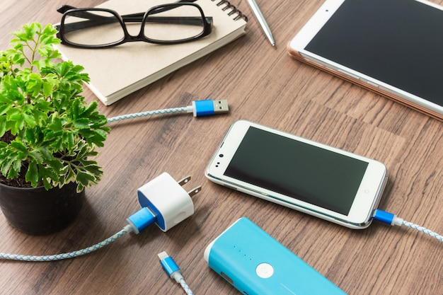 Usbケーブルと机の上のアダプターを備えたスマートフォン Premium写真