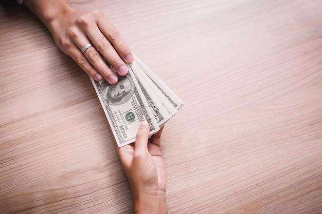 Бизнесмен платит деньги - счета в долларах сша (usd) Premium Фотографии