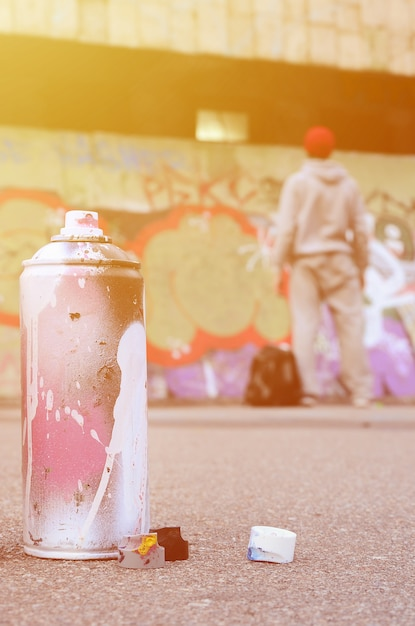 Used aerosol paint spray can with pink and white paint lie on the asphalt Premium Photo