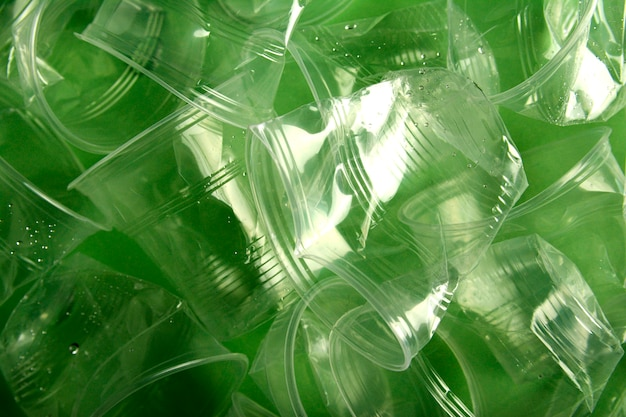 Used plastic cup on green background, recycling concept, minimal design Premium Photo