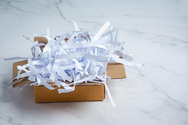 Carta straccia usata e scatole di cartone messe sul pavimento di marmo bianco Foto Gratuite
