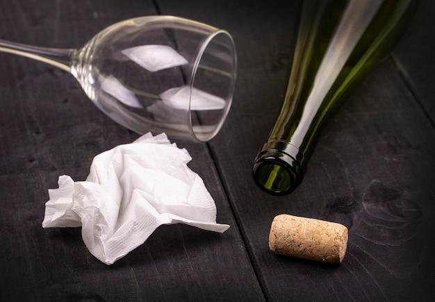 古い木製のテーブルに白いしわくちゃの紙ナプキンとコルクと空のワインボトルを使用しました Premium写真