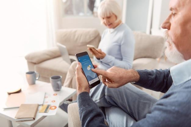 便利なアプリ。居間の肘掛け椅子に座って、電話のアプリケーションで天気予報をチェックしているひげを生やした老人に焦点を当てています Premium写真