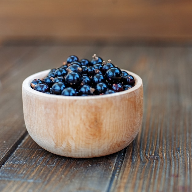 Useful berry. black currants in a wooden bowl. square. Premium Photo