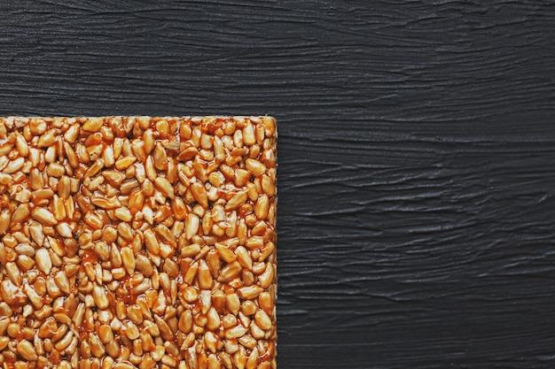 Useful snacks. fitness diet food. boletchik from kozinaki sunflower seeds, energy bars. top view. copy space Premium Photo