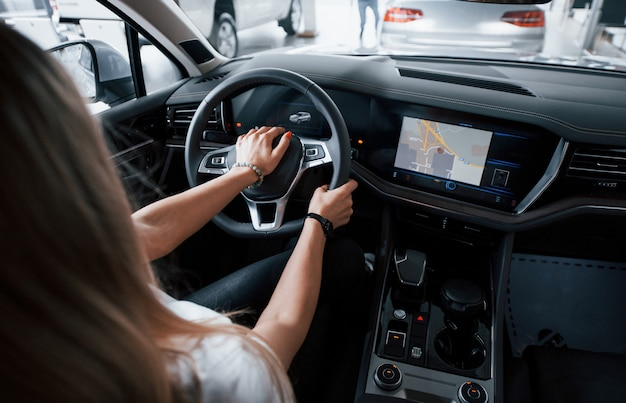 Using gps. girl in modern car in the salon. at daytime indoors. buying new vehicle Free Photo