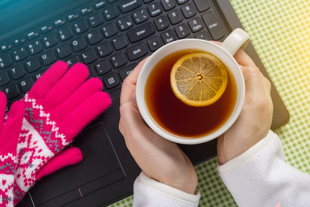 Using laptop in a cold winter - female with gloves on. Premium Photo