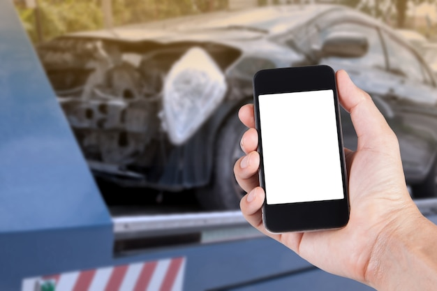 Using smartphone on hand with blurry background of black car on accident on the forklift. Premium Photo