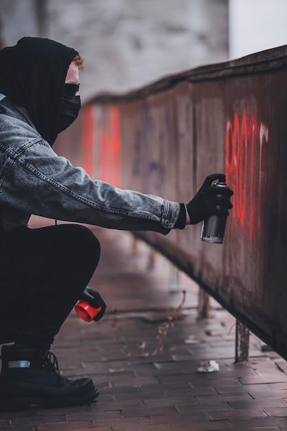 Используйте баллончик с краской, чтобы сделать знак протеста. харизматичный мужчина со скрытой личностью совершает вандализм. Premium Фотографии