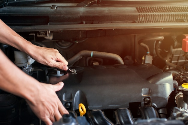 Using wrench to loosen the engine compartment screws Premium Photo