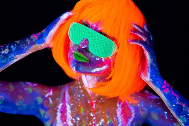 ネオンの光でディスコダンサー。ネオンの光、蛍光メイク、uvでボディーアートデザイン、塗装面、カラフルなメイクアップ、黒の背景に美しいモデルの少女の肖像画のファッションモデルの女性 Premium写真