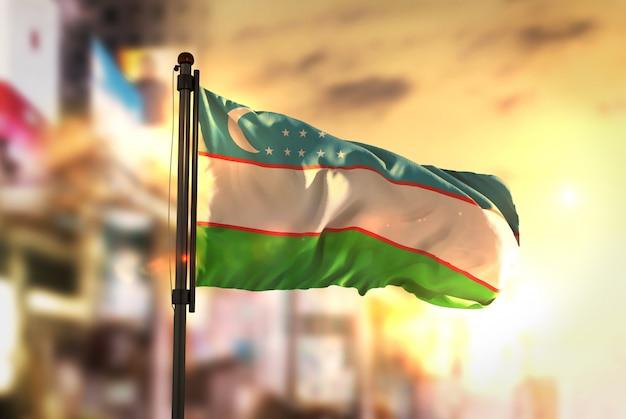 Флаг узбекистана против города размытый фон при восходе солнца Premium Фотографии