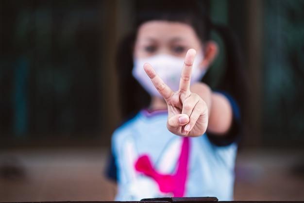 Азиатский маленький ребенок девочка крупным планом поднять два v-образного пальца носить маску для безопасности coronavirus, чтобы поддержать в борьбе с эпидемией болезни концепция covid 19 на дому Premium Фотографии