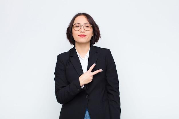 胸の上にvの形を作る手で幸せ、肯定的な成功を感じている若い実業家、白い壁の上の勝利または平和を示す Premium写真