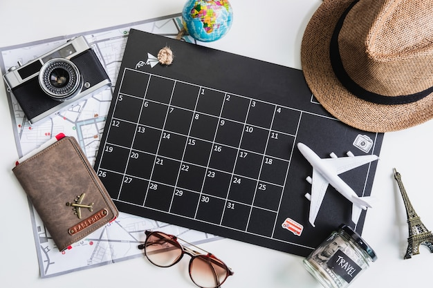 Vacation calendar with camera and travel items, top view Premium Photo